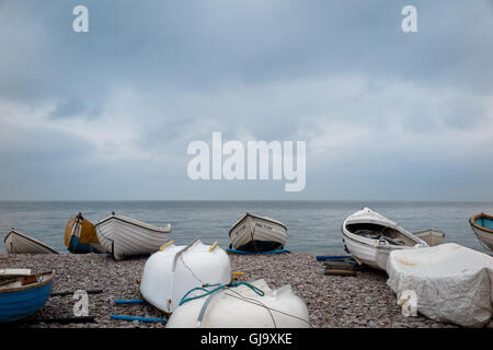 Boats on the beach at Seatown in Devon, winter.  Stormy sky - Stock Photo