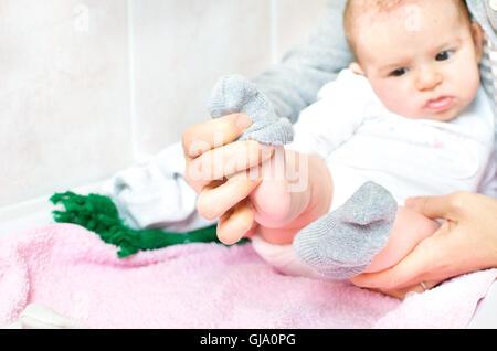 put grey socks at baby newborn - Stock Photo