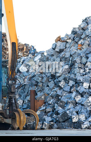 Scrap yard with crane grab and cars crushed into small cubes - Stock Photo