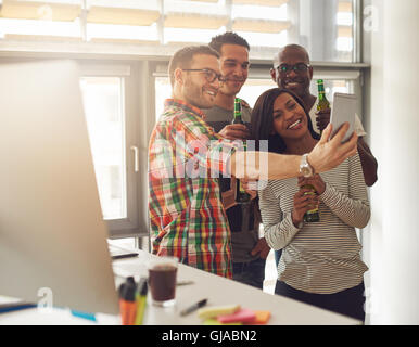 Diverse group of four happy young workers celebrating with beer and taking pictures with camera phone near desk - Stock Photo