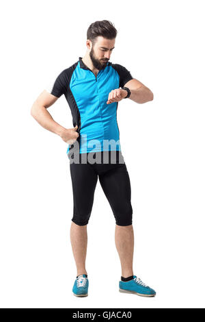 Sport cycling athlete in blue jersey shirt checking time on wristwatch. Full body length portrait isolated over - Stock Photo
