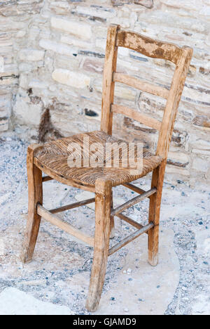 Old shabby wooden straw chair with cobblestone as a background closeup. - Stock Photo