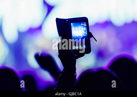 A member of the audience video records a performance at a music concert using their smartphones. - Stock Photo