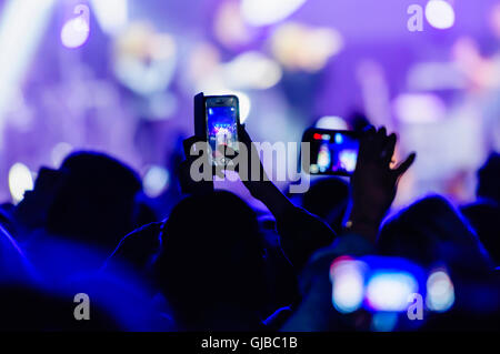 Members of the audience video record a performance at a music concert using their smartphones. - Stock Photo
