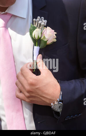 groom wears boutonniere of roses on his jacket before the wedding ceremony - Stock Photo