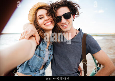 Smiling beautiful young couple hugging and taking selfie on the beach - Stock Photo