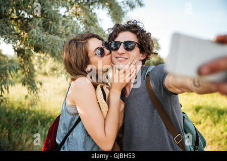 Young smiling happy couple with backpacks hiking in the forest and making selfie - Stock Photo