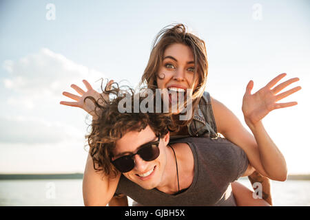 Young happy smiling couple in love piggyback at the beach, cheerful girl is screaming - Stock Photo