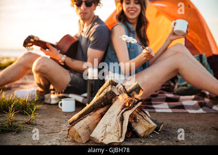 Cropped image of a young couple in love frying marshmallow on bonfire while camping - Stock Photo