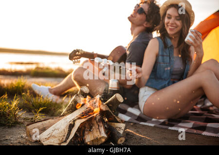 Cheerful beautiful young couple playing guitar and frying marshmallows on bonfire - Stock Photo