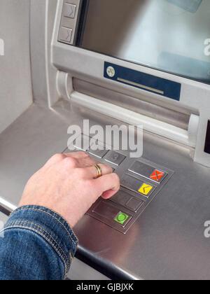 Closeup of woman's hand entering PIN code on ATM machine keypad - Stock Photo