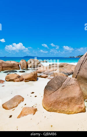 Granite rock formations beach Seychelles in front of blue ocean - Stock Photo