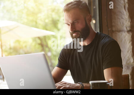Concentrated Bearded Man Wearing Black Tshirt Working Laptop Wood Table Urban Cafe.Young Manager Work Notebook Modern - Stock Photo