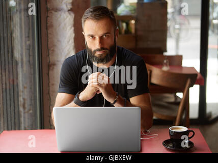 Handsome Young Bearded Businessman Wearing Black Tshirt Working Laptop Urban Cafe.Man Sitting Wood Table Cup Coffee - Stock Photo