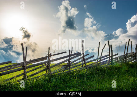 Old wooden fence in front of cloudy sky - Stock Photo