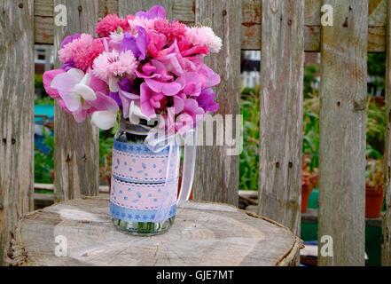 Pink sweet pea and cornflowers arrangement - Stock Photo