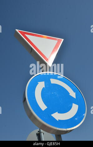 roundabout and give way sign on blue sky - Stock Photo