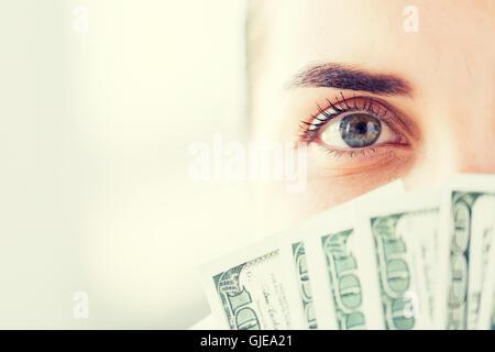 woman hiding her face behind us dollar money fan - Stock Photo