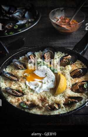 Cooked mussels with boiled egg and spicy rice in the pan,selective focus - Stock Photo