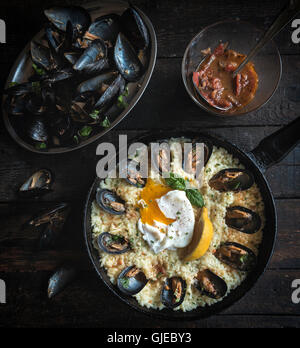 Cooked mussels with boiled egg and rice in the pan on wooden background - Stock Photo
