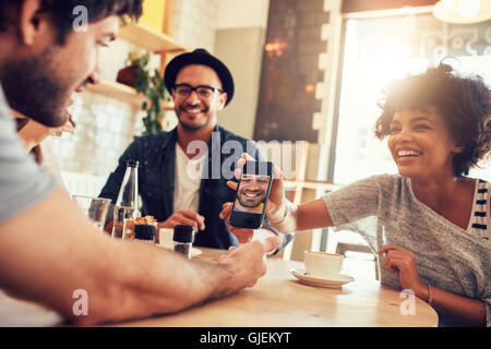 Portrait of happy young friends in cafe and looking at the photos on smart phone. Group of mixed race people sitting - Stock Photo