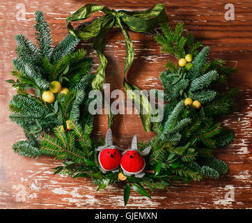 Christmas floral wreath decoration with baubles, red bow, holly and winter greenery over oak background. - Stock Photo