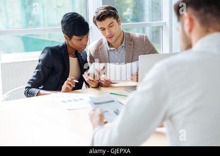 Group of young businesspeople having meeting at the table in modern office