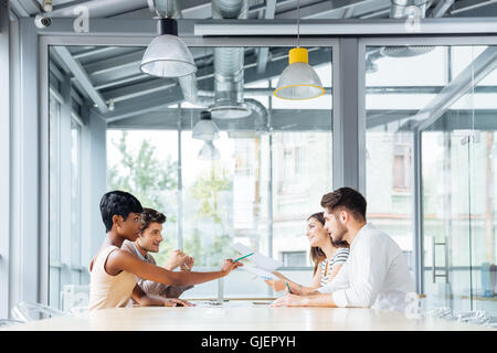 Group of young businesspeople talking and working together in conference room - Stock Photo