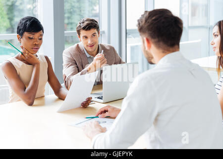 Group of young businesspeople working with laptop at meeting in office - Stock Photo