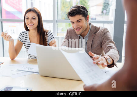 Smiling woman and man working and discussing project and using laptop in the office - Stock Photo