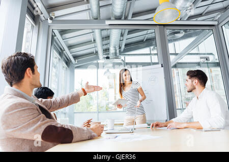 Cheerful pretty young woman making presentation using flipchart in office - Stock Photo