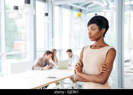 Pensive african american young businesswoman standing with arms crossed and thinking in office - Stock Photo