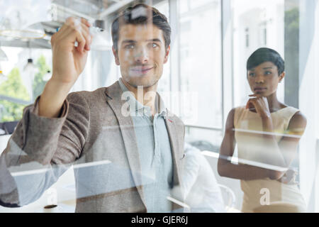 Concentrated young businessman working with african businesswoman and writing on transparent board in office - Stock Photo