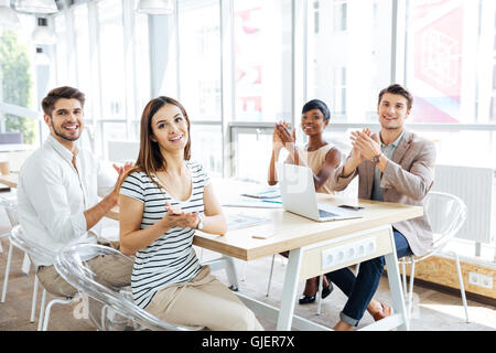 Multiethnic group of happy young business people applauding at meeting in office - Stock Photo