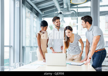 Multiethnic group of happy young business people standing and creating presentation with laptop in office