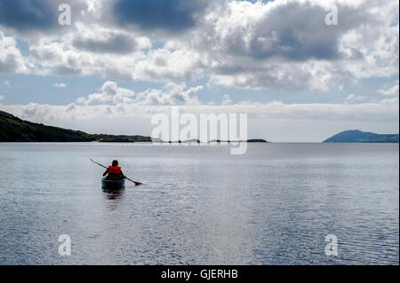 A female kayaker paddles away from the sea shore on a calm sea in West Cork, Ireland. - Stock Photo