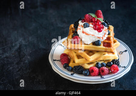 Traditional Belgium waffles with berry fruits and ice cream on top,selective focus and empty space - Stock Photo