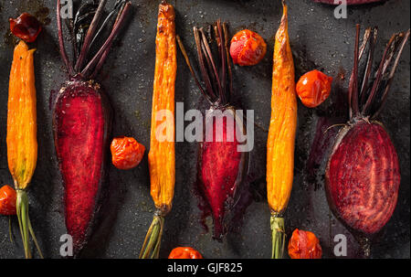 Baked carrots and beets with tomatoes - Stock Photo