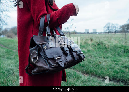 Woman in red overcoat holding a Mulberry Roxanne leather handbag - Stock Photo
