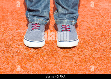 Boy in blue sneakers and jeans standing on red playground background. Close up leg's shot. Top view. - Stock Photo