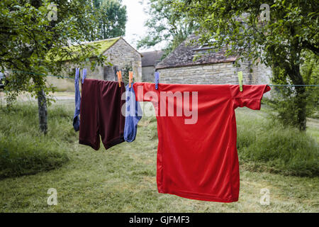 House of little football player. Boy's sport outfit on drying line outdoor, - Stock Photo