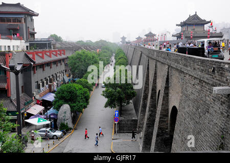 August 19, 2015. Xian, China.  Chinese tourists walking on the Xian city wall as it rises up above the streets in - Stock Photo