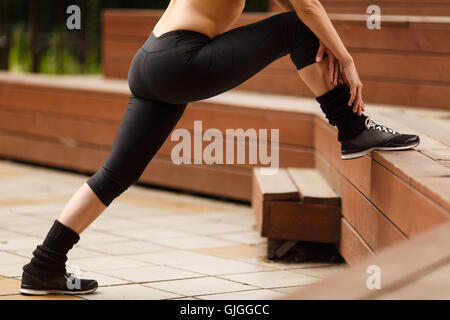 Fitness woman stretching legs before training outdoors - Stock Photo