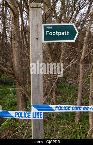 Footpath signpost has police blue and white police line tape wrapped round it - Stock Photo