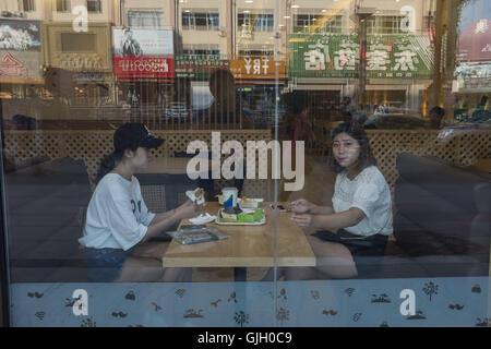 Hunchun, Jilin Province, China. 1st Aug, 2016. Two young girls eating hamburgers in a fast food restaurant in Hunchun, - Stock Photo