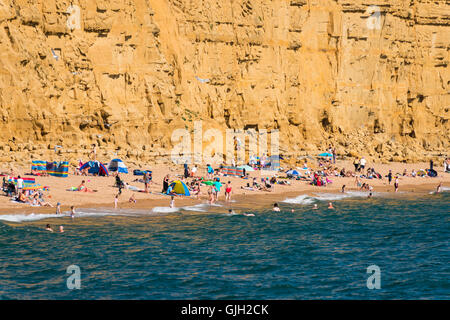 West Bay, Dorset, UK. 16th August, 2016. Landslide danger.  A packed beach below East Cliff at West Bay in Dorset - Stock Photo