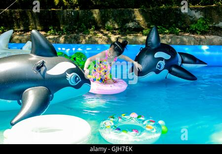 Chongqing, China's Chongqing Municipality. 17th Aug, 2016. A kid plays in an inflatable swimming pool in Zhuxi River - Stock Photo