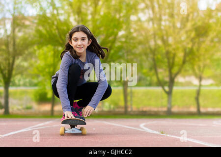 Girl skateboarding in park - Stock Photo