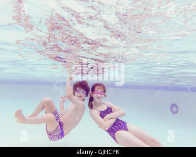 Boy and girl messing about underwater in swimming pool - Stock Photo