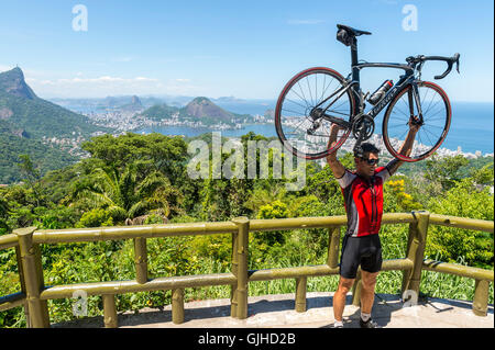 RIO DE JANEIRO - FEBRUARY 24, 2015: Cyclist poses with his bicycle aloft after making the steep ascent to the Vista - Stock Photo